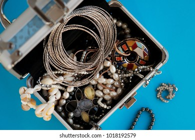 Jewelry and bijouterie. Lots of jewelry in the box. View from above. Design, style and fashion jewelry. Bijouterie of different kinds. Beads made of shells, silver bracelet in a box.