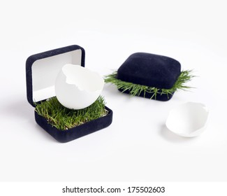 A jewelry box with a broken egg inside.