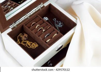 jewelry box with jewelry on silk textile background.