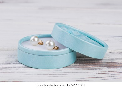 Jewelry box with pearl earrings. Blue gift box with golden earrings on wooden background. Beautiful gift for Valentines Day.