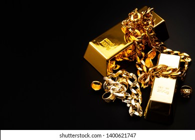 Jewelry buyer, pawn shop and buy and sell precious metals concept theme with a pile of golden rings, necklace bracelet and gold bullion isolated on black background with copy space