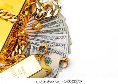 Jewelry buyer, pawn shop and buy and sell precious metals concept theme with a pile of cash in US dollars, golden rings, necklace bracelet and gold bullion isolated on white background with copy space