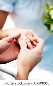 Jewelry, couple, love and wedding concept - close up of man and woman hands with engagement diamond ring in woman's finger.