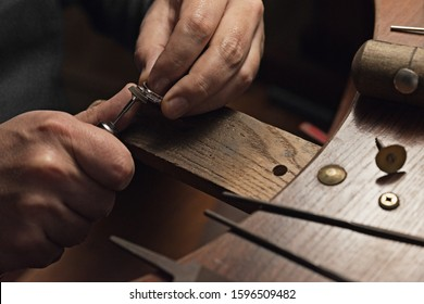 Jewelry craftsmanship. Handmade. Jeweler at work. The jeweler polishes a white gold ring with diamonds. Jeweler polishes the gold ring holding the ring in one hand and the polishing tool in the other.