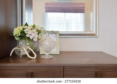 Jewelry crystal jar with picture frame and flowers on the wooden table