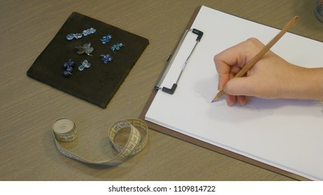 Jewelry designer at work in studio, sketching designs for unique handmade earrings