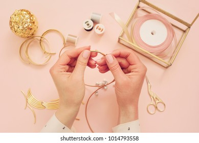 Jewelry designer workplace. Woman hands making handmade jewelry. Freelance fashion femininity workspace in flat lay style. Pastel pink and gold - Shutterstock ID 1014793558