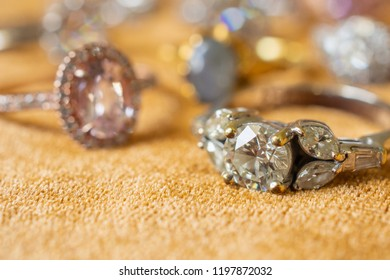Jewelry diamond rings on golden fabric background close up