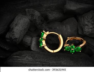 jewelry earrings witht gem emerald on dark coal background