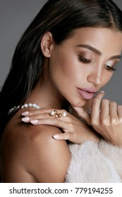 Jewelry Fashion. Woman In Luxury Jewels And Fur. Portrait Of Sexy Female Model With Beauty Makeup, Pastel Nails Wearing Pearl Jewelry And White Fur Coat. High Quality Image.
