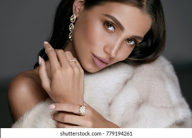 Jewelry Fashion. Woman In Luxury Jewels. Glamour Female Model With Beauty Face Makeup Wearing Expensive Gold Jewelry And Stylish Beige Mink Fur Coat. High Quality Image.