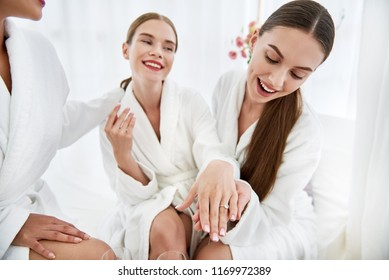 Jewelry from fiance. Beautiful young women in white bathrobes having bachelorette party at spa salon