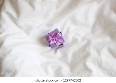 Jewelry Gift box. Present box for holidays, decorated with purple ribbon bow. Valentine's Day gift, International Women's Day gift over white bed linen background. Valentine's Gift Flatlay.