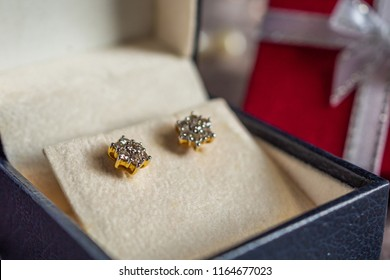 Jewelry gold diamond earring with gift box background
