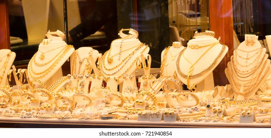Jewelry gold necklaces rings bracelets watch wealth,  Jewellery shops on Ponte Vecchio bridge in Florence, Italy, Gold background.