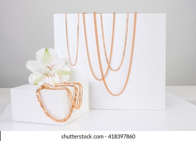 Jewelry gold set of chains and bracelets next to white lily on white background