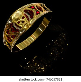 Jewelry gold skull ring with diamond and red gems. Antiques fingers ring from pirate treasure or hoard may be magic vampire artifact. Luxury bijouterie band for biker with reflection. 3D rendering.