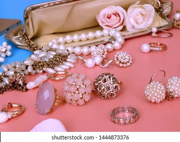 Jewelry gold  white pearl Luxury Glamour fashion  costume jewelry cosmetics cases  rings earrings bracelet with   red roses on blue and pink coral background women accessories