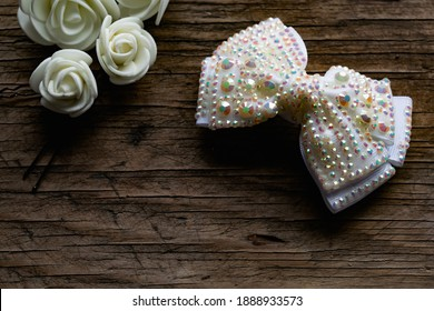 Jewelry and hair accessories. Elegant bow with holographic stones and rhinestones with a pink tint. There are cute milky roses around. Costume jewelry on an old wooden background covering