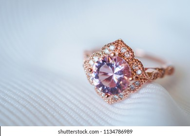 Jewelry luxury pink gold sapphire gemstone ring on white fabric background