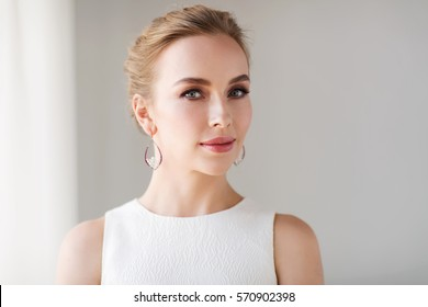 jewelry, luxury, wedding and people concept - smiling woman in white dress wearing pearl earrings