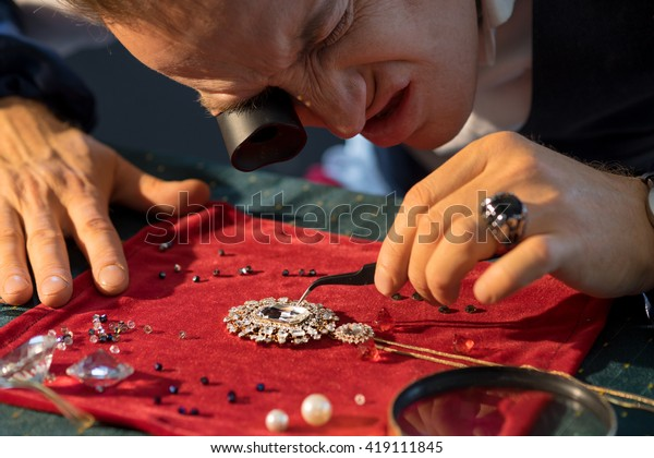 https://image.shutterstock.com/image-photo/jewelry-maker-considers-jewel-600w-419111845.jpg