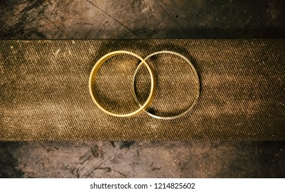 jewelry making at the jeweler's workplace.  blanks of wedding rings made of yellow and white gold lie on a large file covered with gold sawdust files