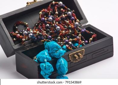 Jewelry old box and blue bead necklace. Isolated on a white background. Black casket