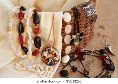 Jewelry on silk fabric. Beads, pendants, bracelet in a wicker box. Bijouterie and silk fabric look stylish. Design and fashion jewelry. A lot of jewelry. Pearl beads on silk fabric.