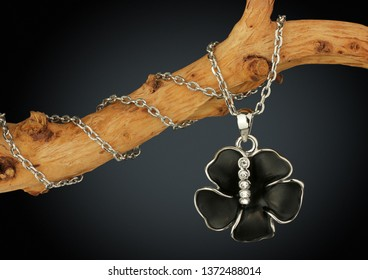 Jewelry pendant shape of black flover on twig, on dark