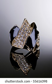 Jewelry photography. Gold ring with crystals on gradient reflective surface.