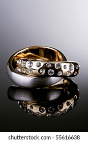 Jewelry photography. Gold ring with Diamonds and silver ring on gradient reflective surface.