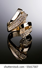 Jewelry photography. Gold ring with diamonds on gradient reflective surface.