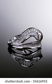 Jewelry photography. Silver ring with crystals on gradient reflective surface.