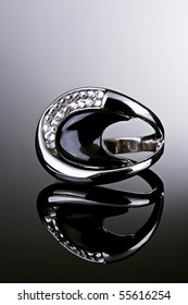 Jewelry photography. Silver ring with diamonds on gradient reflective surface.
