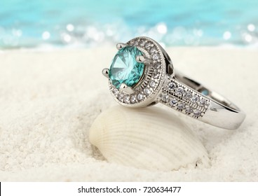 Jewelry ring with aquamarine gem on sand beach background