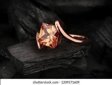 jewelry ring with big topaz gem on dark coal background