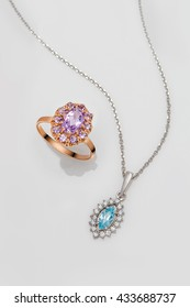Jewelry set of gold ring and silver pendant with pink and blue topazes on grey background