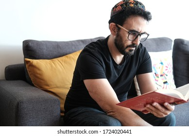 Jewish bearded man sitting and prays while reading holy book of Torah. The man is wearing a simbolic and big  kippah on his head. The man appears sitting in he's home coach