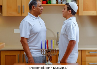 Jewish Boy and dad with deeper skin tones recited blessings on Chanukah menorah and Sing the traditional Hanukkah songs. Maoz Tzur traditional Chanukah song is sung after the lighting of the Menorah.