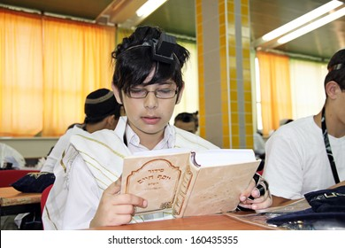 Jewish Boy reads a prayer book in the school synagogue