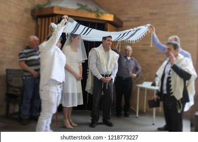 Jewish bride and a bridegroom married in a modern Orthodox Jewish wedding ceremony in a synagog.