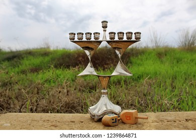 Jewish candlestick Menorah in style Jewish star Magen David and Wood Dreidels (toy Hanukkah, holiday symbol). Image of Jewish holiday Hanukkah, Israel