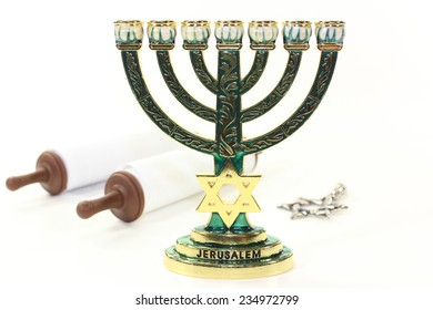 Jewish candlestick and Torah scroll in front of white background