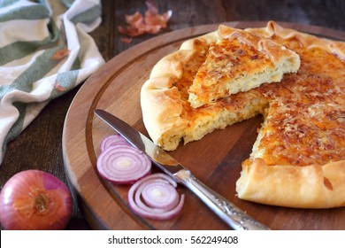 Jewish cuisine: onion cheese pie on wooden chopping board
