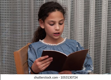 Jewish Family Celebrating Passover.Jewish gir reads from the Haggadah as they celebrate Seder. The feast is celebrated on the first night of Passover, holiday commemorating the Jews exodus from Egypt.