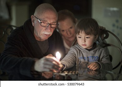 Jewish Family lighting Hanukkah Candles in a menorah for the holdiays