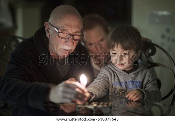 Jewish Family lighting Hanukkah Candles in a menorah for the holdiays