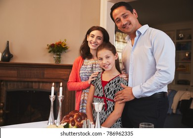 Jewish family stand looking to camera before Shabbat meal
