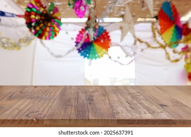 Jewish festival of Sukkot. Traditional succah (hut) with decorations. Empty wooden old table for product display and presentation. - Shutterstock ID 2025637391